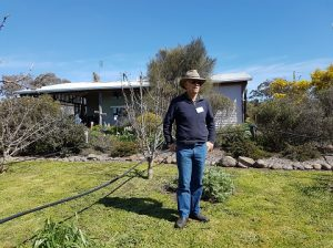 Hugh standing near the fruit trees doing a site visit