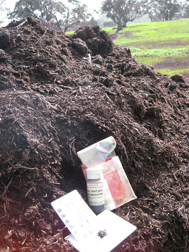 A pile of woody compost with a pH kit