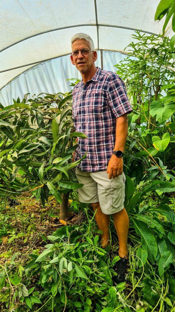 Hugh admiring a dwarf Irwin mango tree